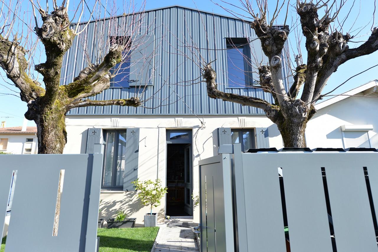 Façade sud de la maison des charmilles. Surélévation en bardage métallique gris moyen, et rez-de-chaussée réhabilité: pierre et bois. / © Justine Reverchon Architecte