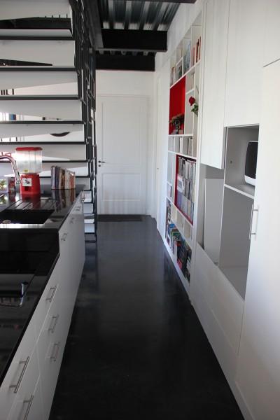Maison des charmilles - escalier et cuisine - Cuisine sous l'escalier, et mur de rangements/cuisine. Sol en béton ciré / © Justine Reverchon Architecte