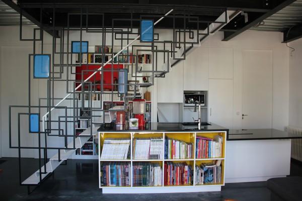 Maison des charmilles - Mondrian - Escalier suspendu à la trémie de l'étage, cuisine/bibliothèque intégrée dessous, et mur de rangements en fond, portes toute hauteur. / © Justine Reverchon Architecte